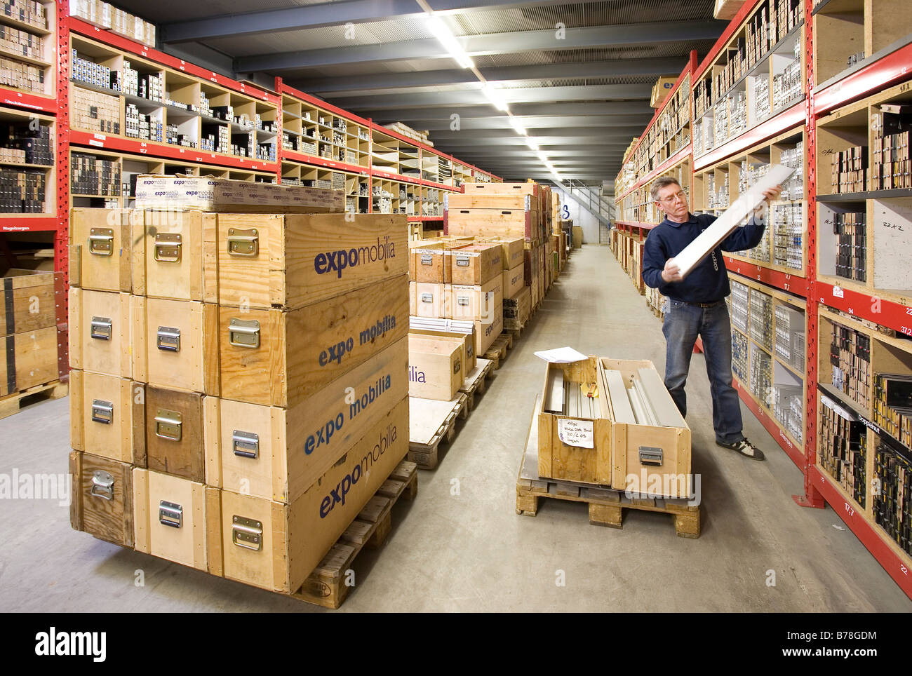 Warehouse manager for the Expomobilia company which constructs exhibition booths sorting building material in the - Stock Image