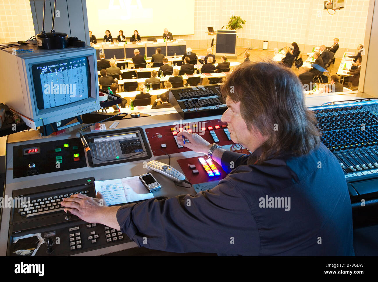 Sound and light director in the congress center of the Messe Schweiz in the sound and light control booth over a - Stock Image