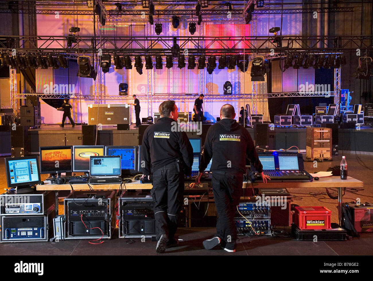 Employee of the event technology company, Winkler, during the setting up of sound and light equipment on the stage - Stock Image