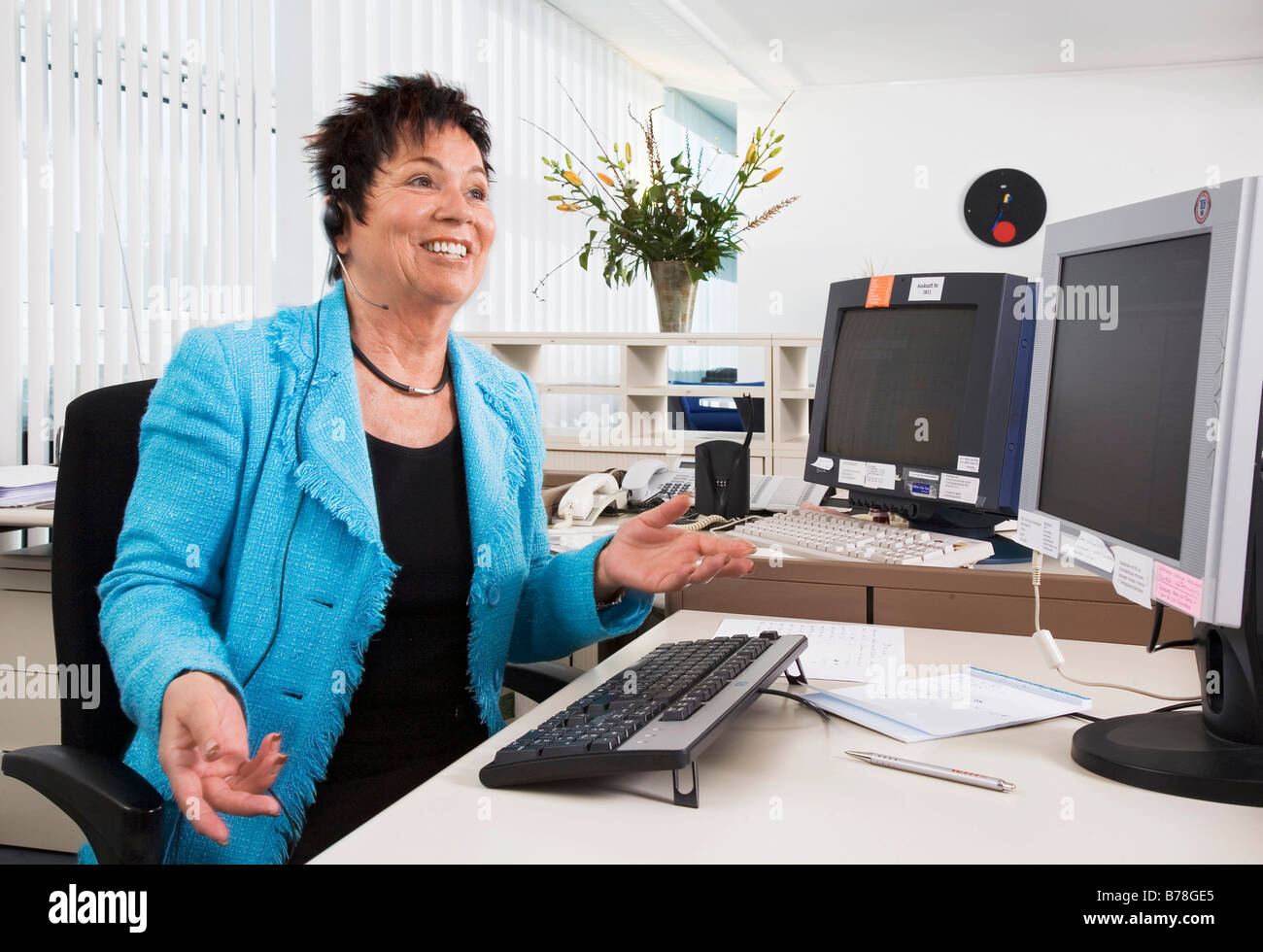 Receptionist of the Messe Schweiz AG talking to a caller over a headset, Zurich, Switzerland, Europe - Stock Image