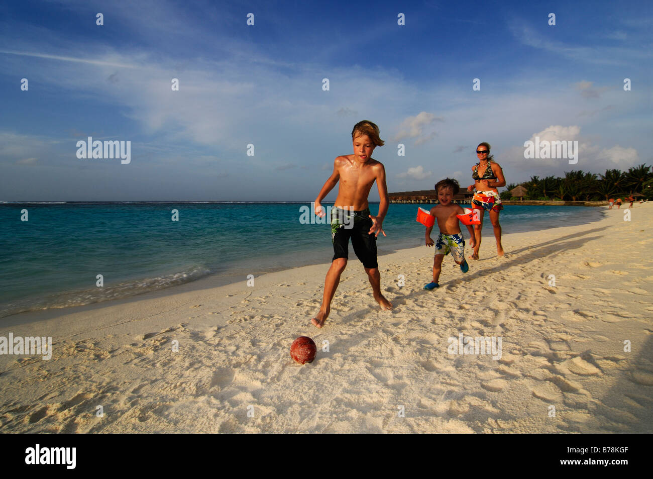Children playing football on the beach of Laguna Resort, The Maldives, Indian Ocean - Stock Image