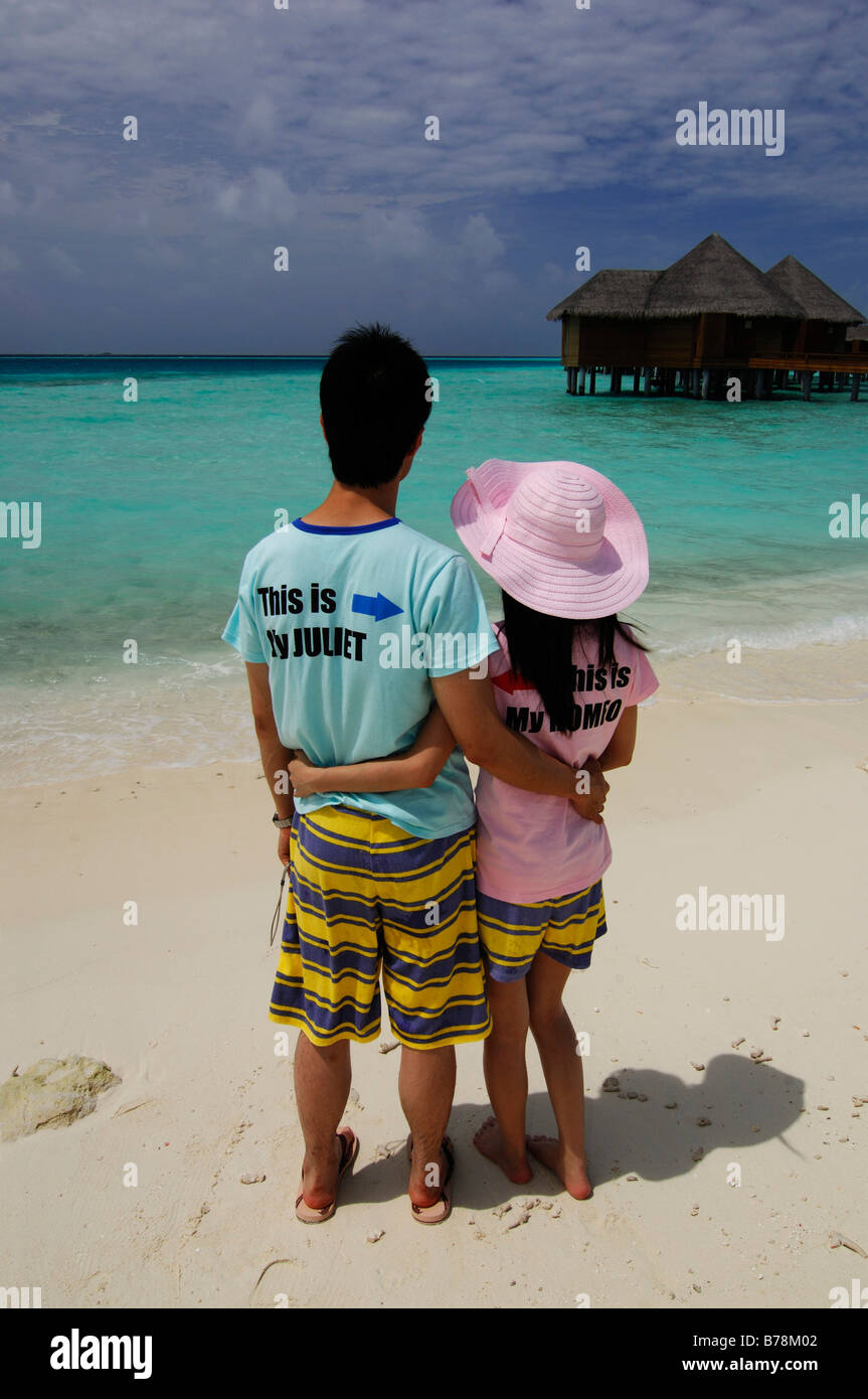 Japanese honeymooners on the beach wearing Romeo and Juliet T-shirts in Baros Resort, The Maldives, Indian Ocean - Stock Image