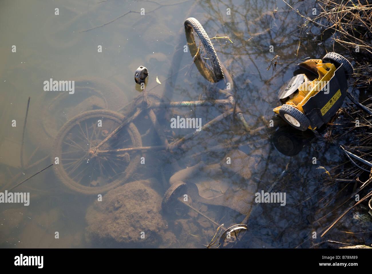 Old bike dumped in river - Stock Image