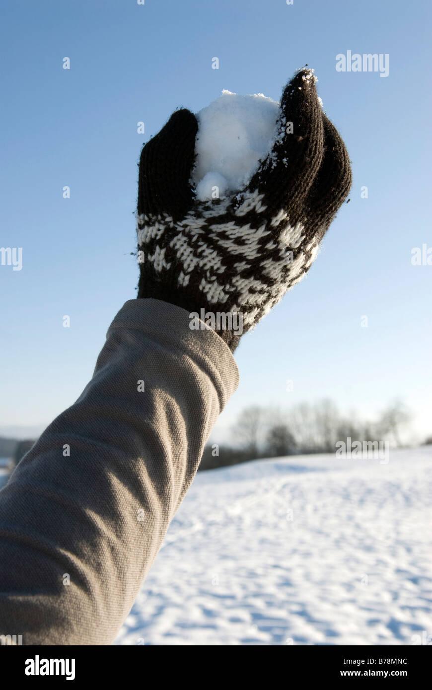 Human hand holding snowball, close-up - Stock Image