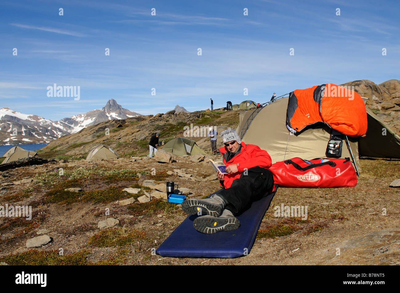Trekker, tent, camping in Ikasartivaq-Fjord, East Greenland, Greenland - Stock Image