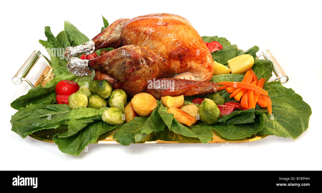A festive platter,loaded with a roasted turkey and an assortment of delicious vegetables. - Stock Image