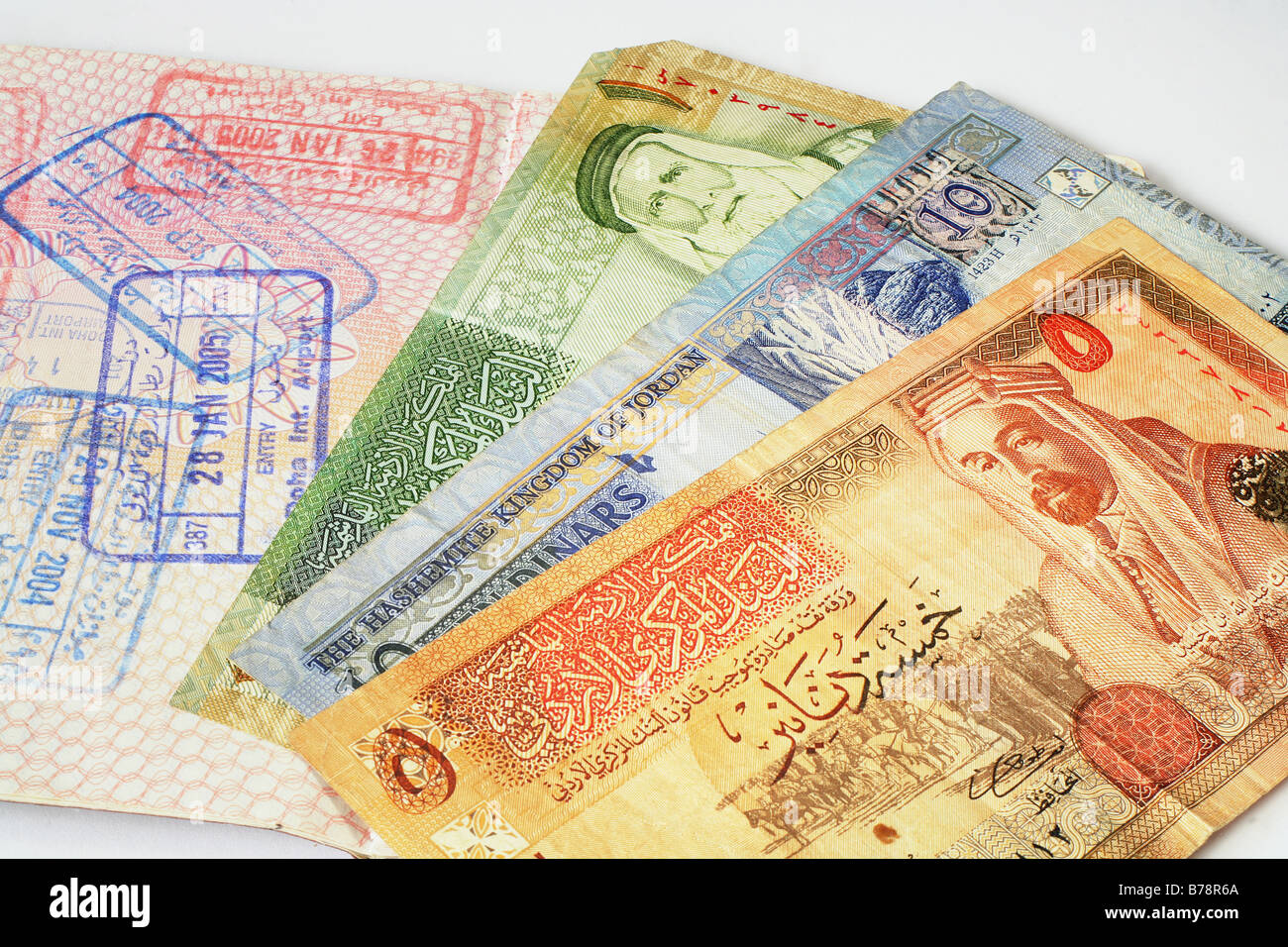 A passport with Middle Eastern visa stamps and a bunch of Jordanian currency notes. - Stock Image