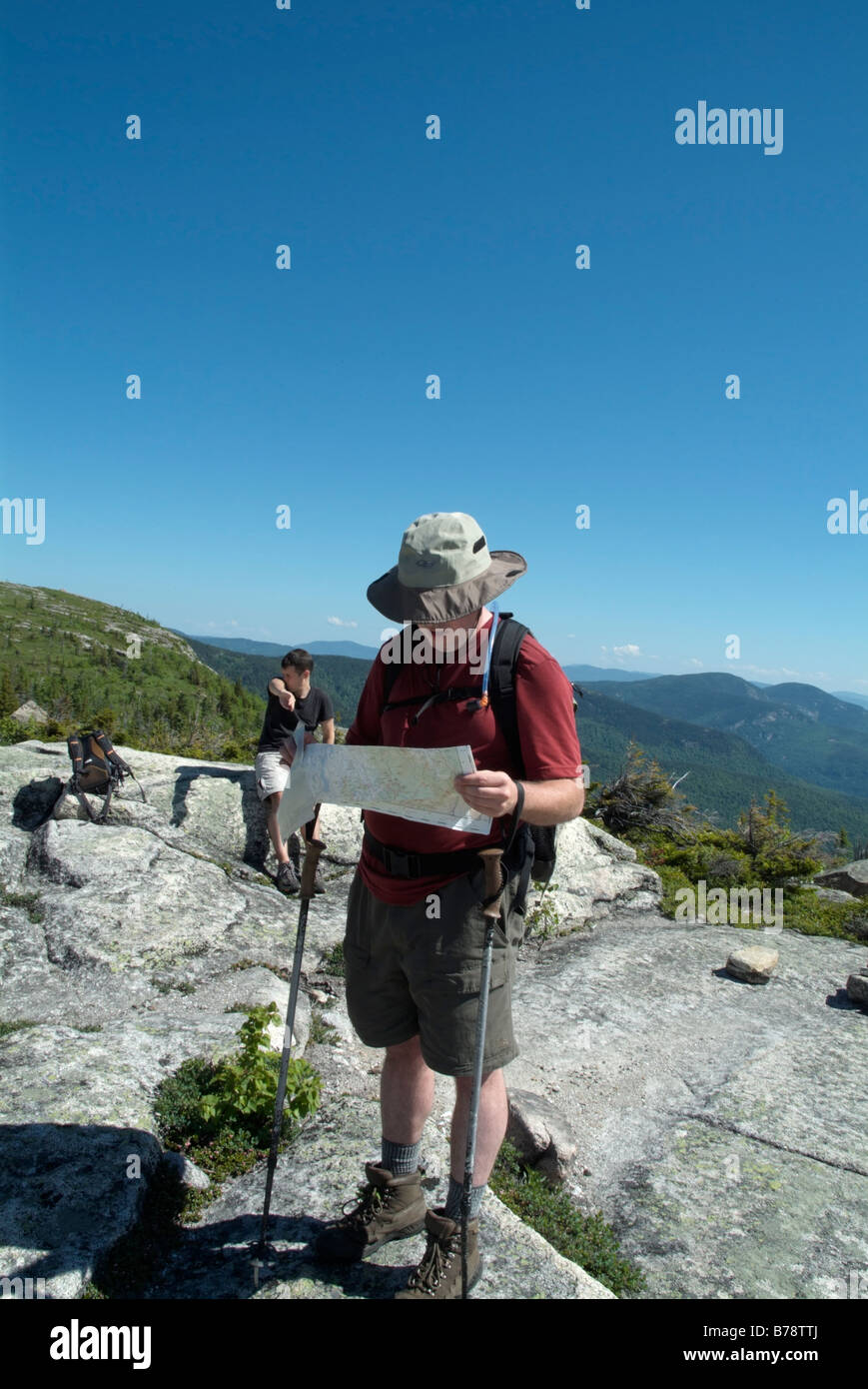 Hiker reading map on Baldface Cirlce Trail during the spring months in the White Mountains New Hampshire USA - Stock Image