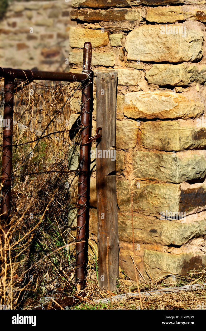 Rusted steel gate of a sandstone kraal - Stock Image
