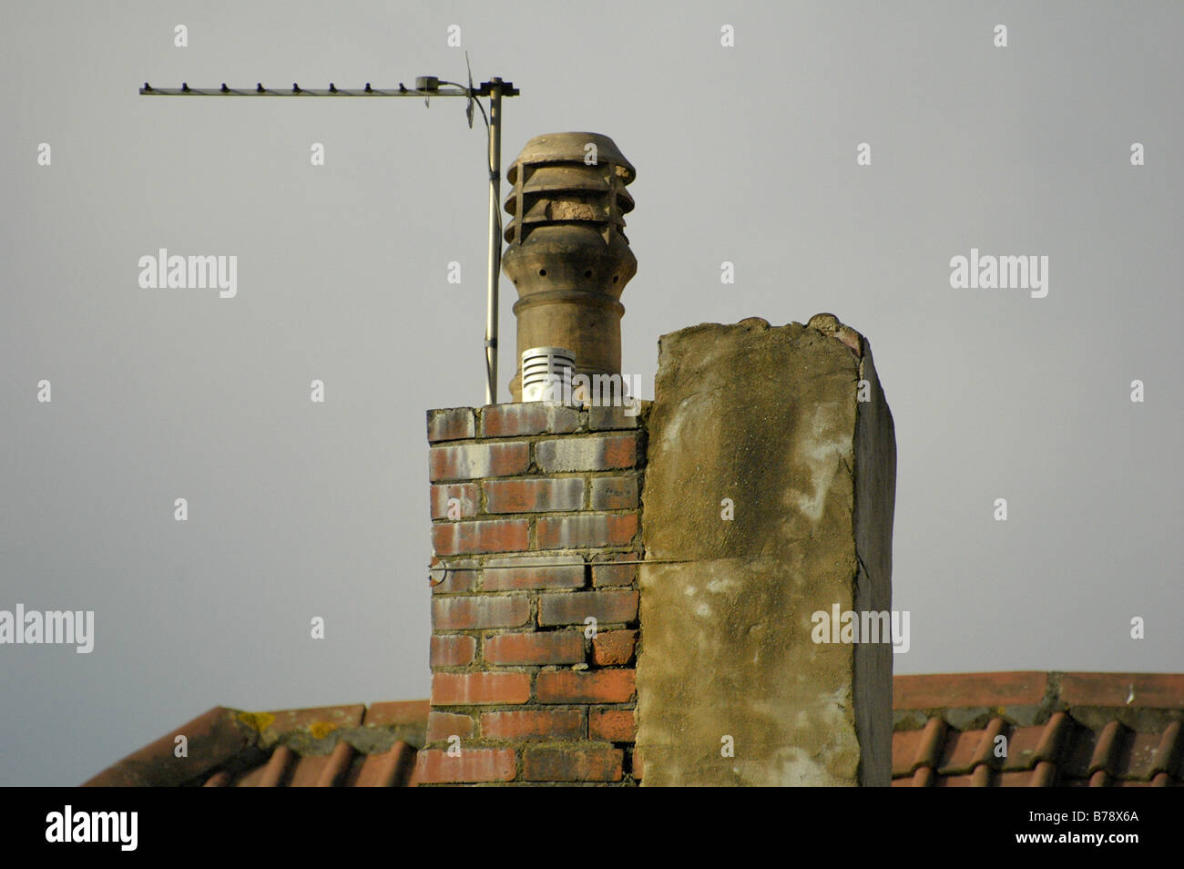 Decrepit looking chimney stack on a roof with an Ariel attached - Stock Image
