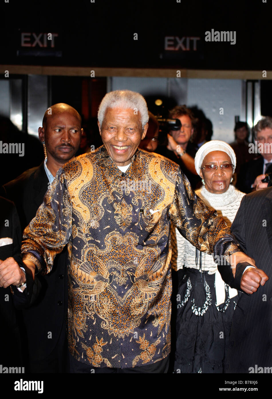 Smiling Nelson Mandela entering a room with his entourage at George Bizos fund raising function in Johannesburg - Stock Image
