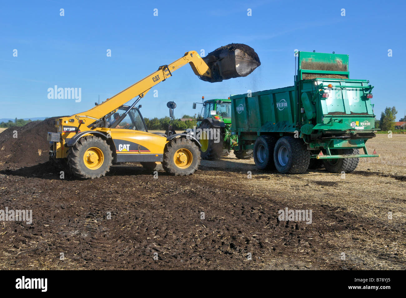 A CAT telescopic  handler  (TH330B) filled with a compost spreader. Stock Photo