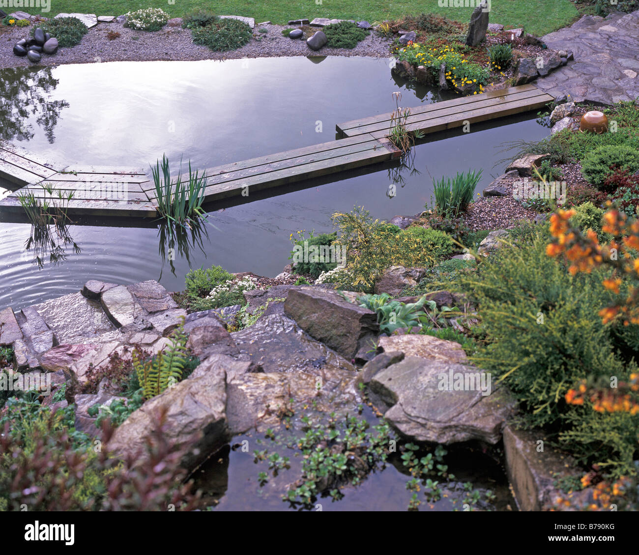 SAWN SOFTWOOD PLANKS MALE A BRIDGE ACROSS THIS NEW POND - Stock Image