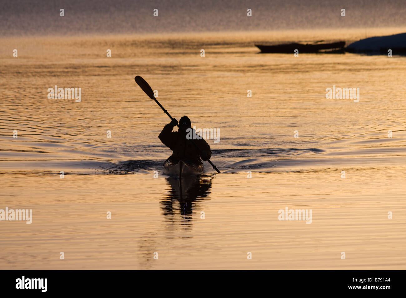 A man and his reflection kayaking at sunrise in winter on Lake Tahoe California Stock Photo