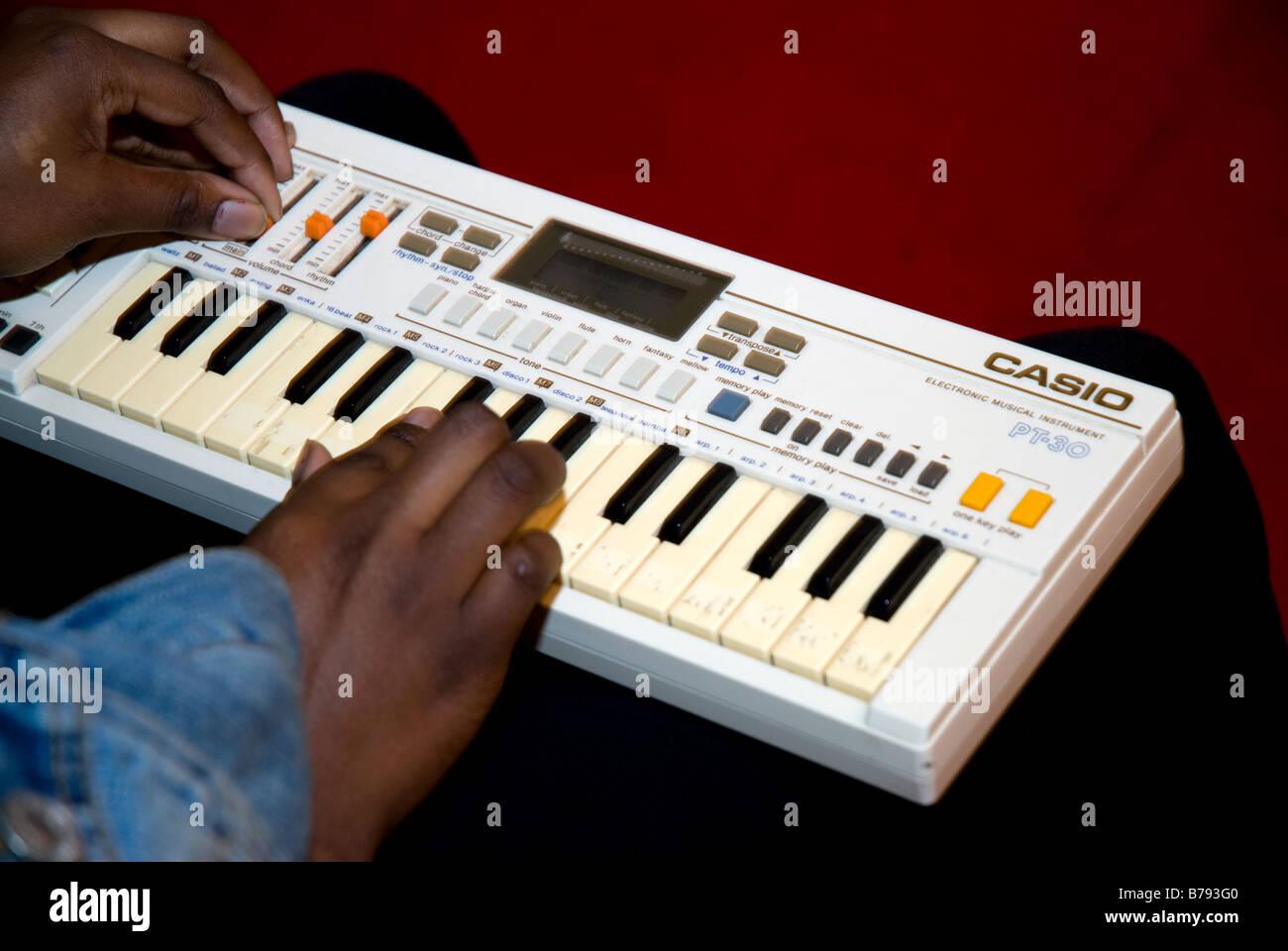 Playing a mini Casio keyboard - Stock Image