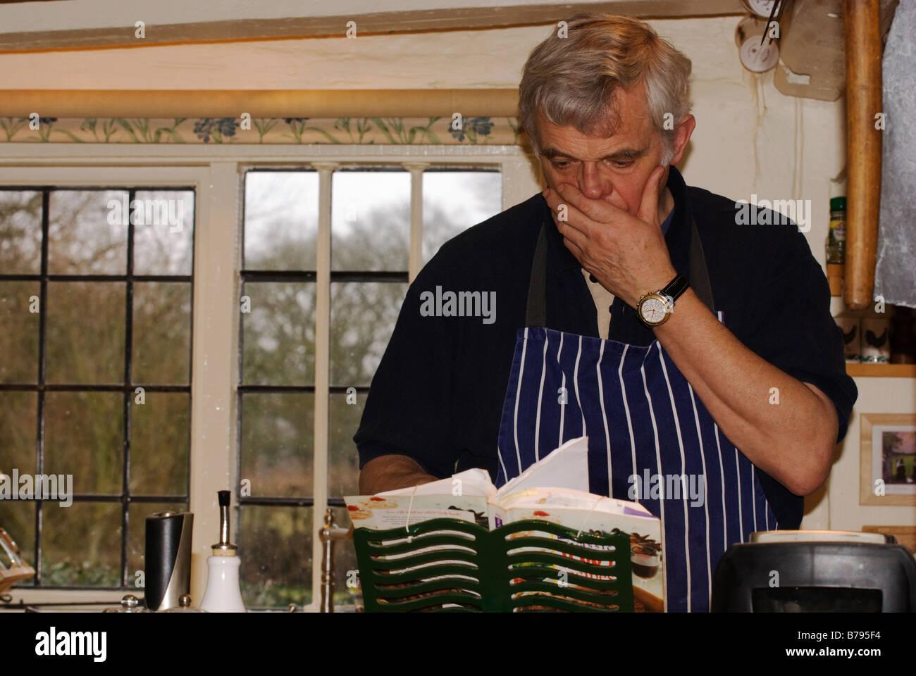 man deliberating over recipe book - Stock Image
