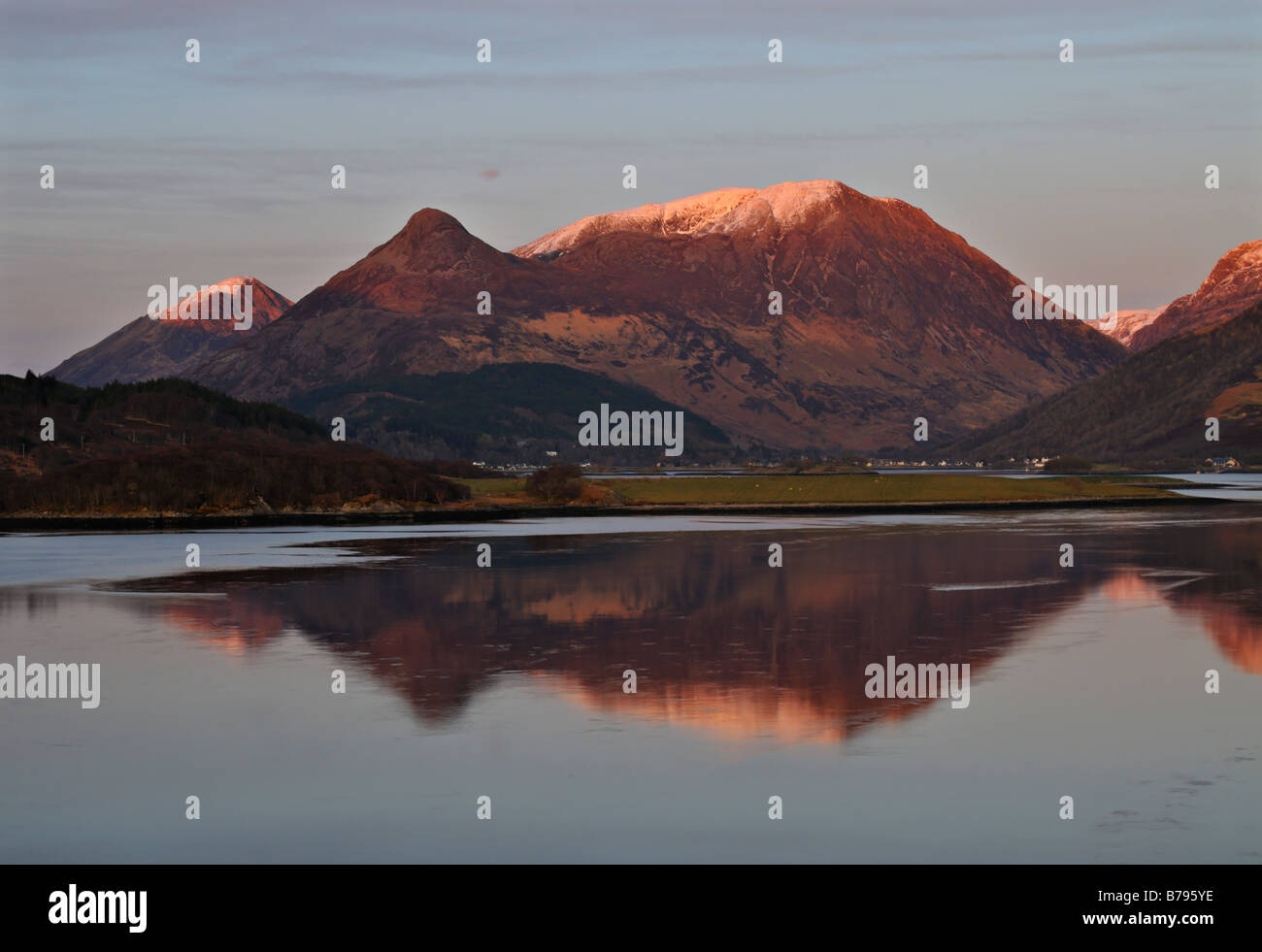 Warm evening light on the calm waters of Loch Leven and the snow capped Glencoe hills Glencoe Argyll western Scotland - Stock Image