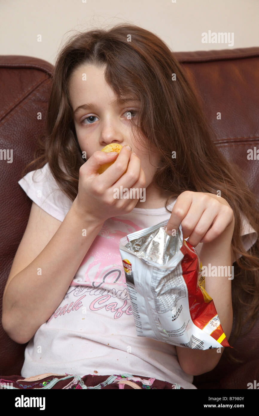 a young girl eating crisps / fries - junk food snack - Stock Image