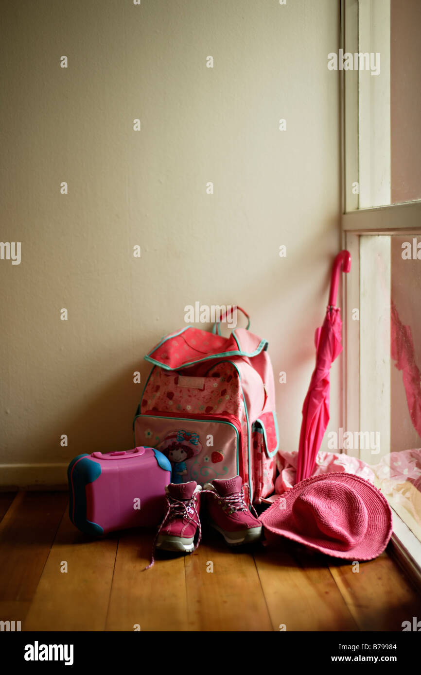 Little girl s pink collection by door coat hat umbrella bag boots and lunchbox - Stock Image