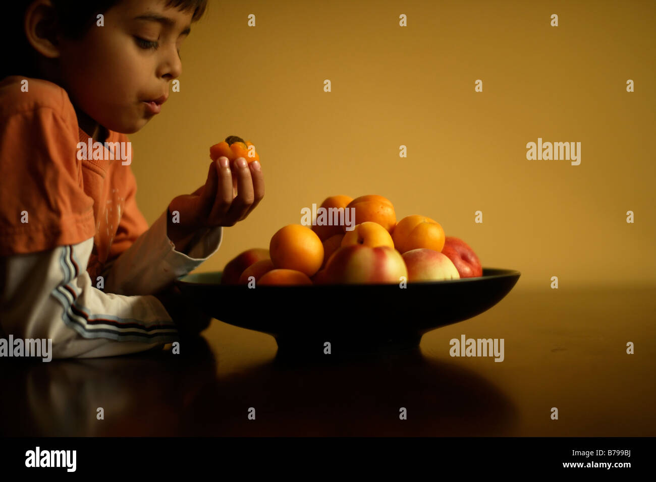 Six year old boy eats apricot - Stock Image