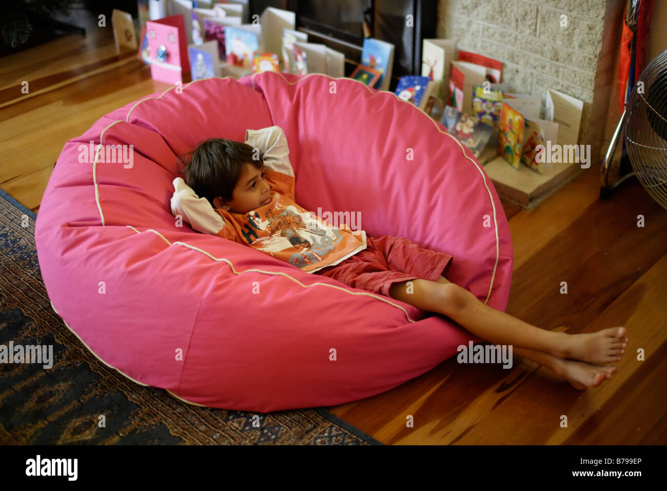 Six year old boy sits in pink beanbag and watches tv - Stock Image
