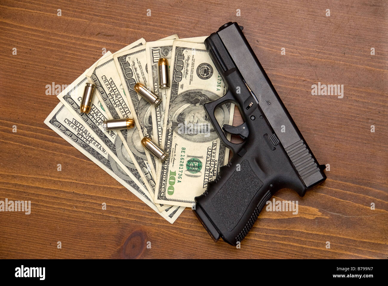 Bullets cash and a gun on a table - Stock Image