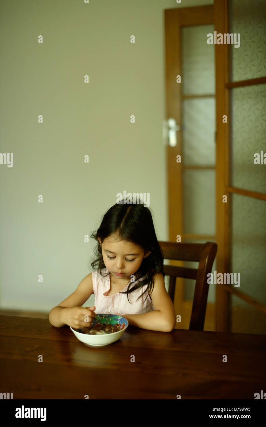 Five year old girl sits at a wooden table and eats a bowl of cereal - Stock Image