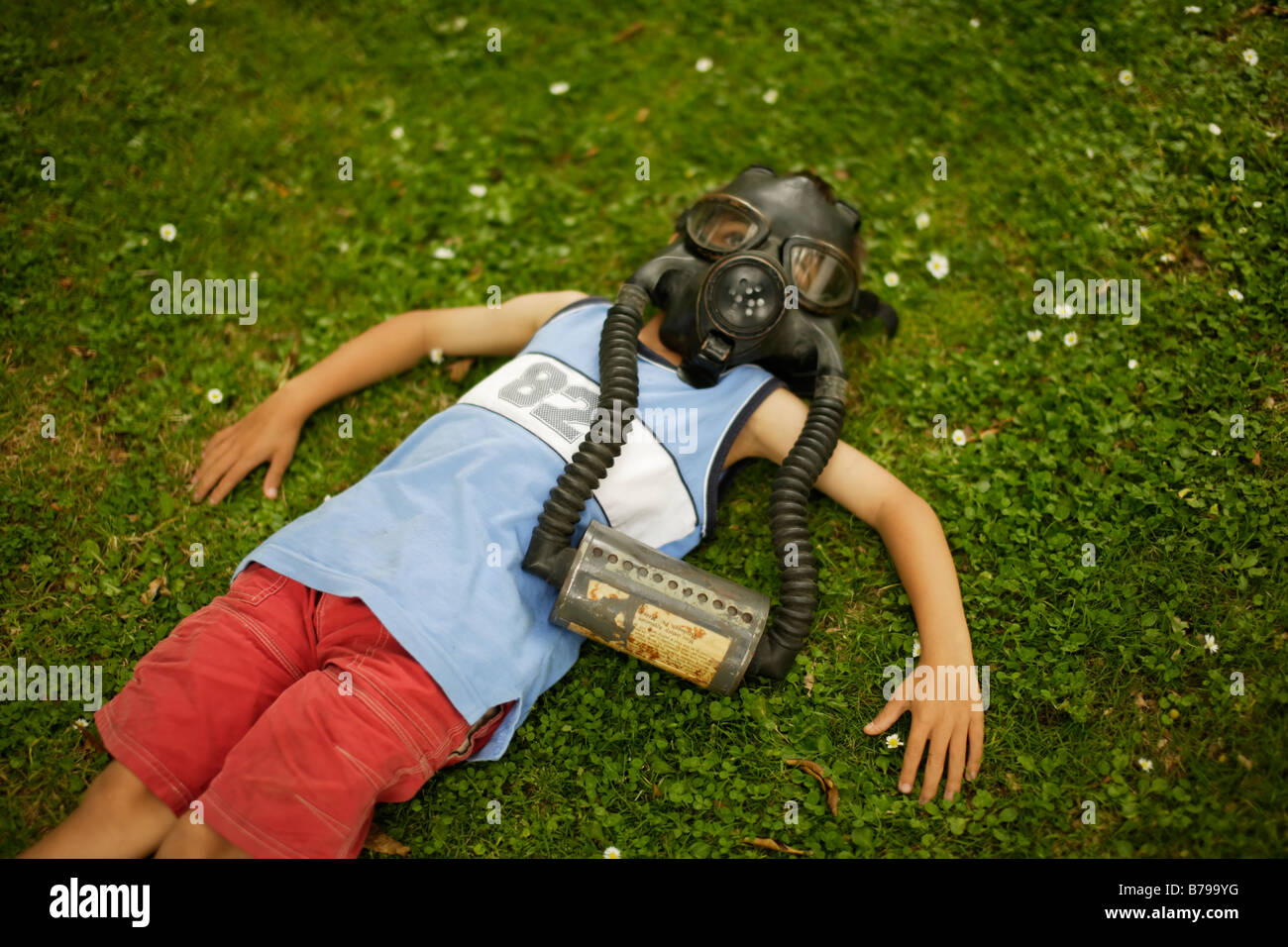 Six year old boy lies on green grass wearing gas mask - Stock Image