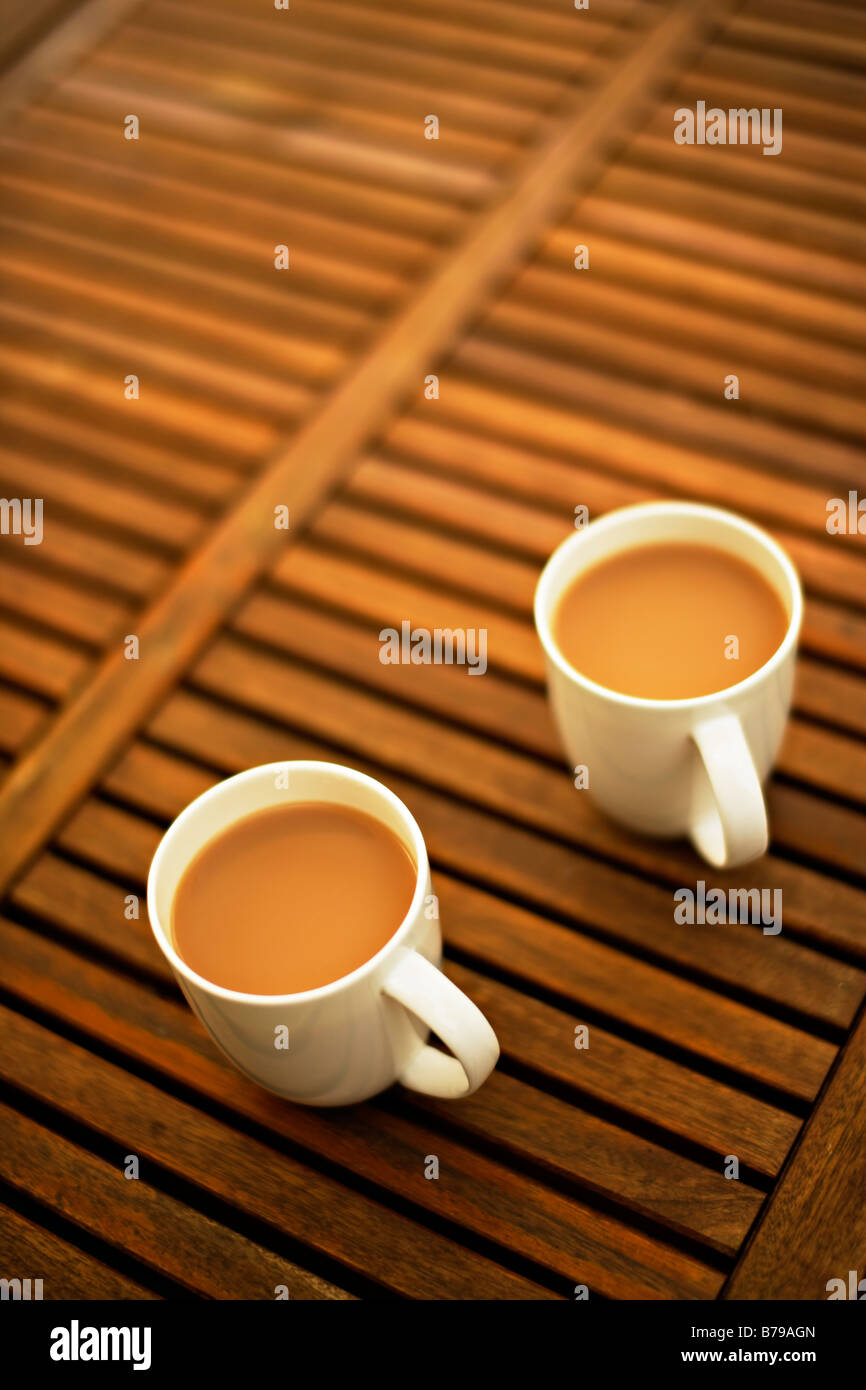 Two mugs of tea on a wooden garden table - Stock Image