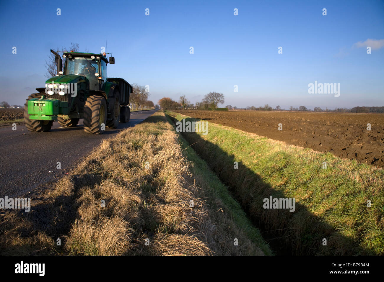 A TRACTOR DRIVES ALONG THE COUNTRY ROAD PAST PLOUGHED FIELDS IN THE WINTER IN ENGLAND UK Stock Photo