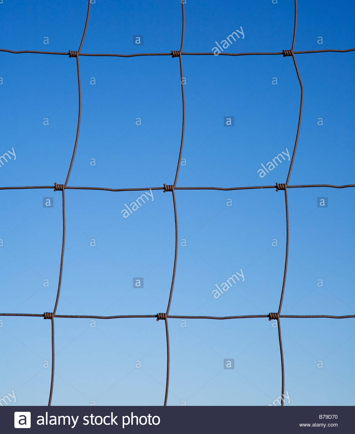 Rusty woven wire fence blue sky background - Stock Image