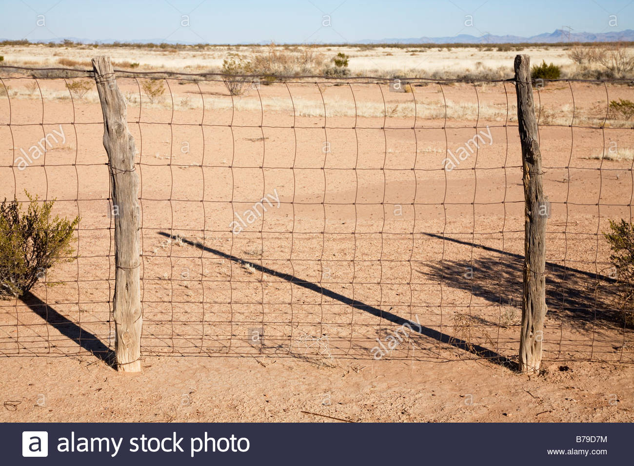 Rusty woven wire fence wooden posts - Stock Image