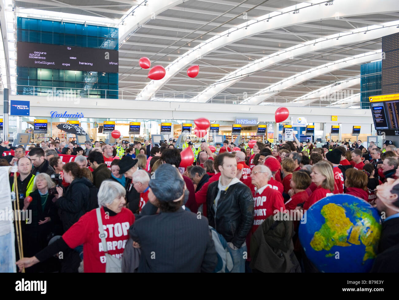 Activists opposed to a third runway at Heathrow staging a 'flash mob' protest inside the airport's Terminal - Stock Image