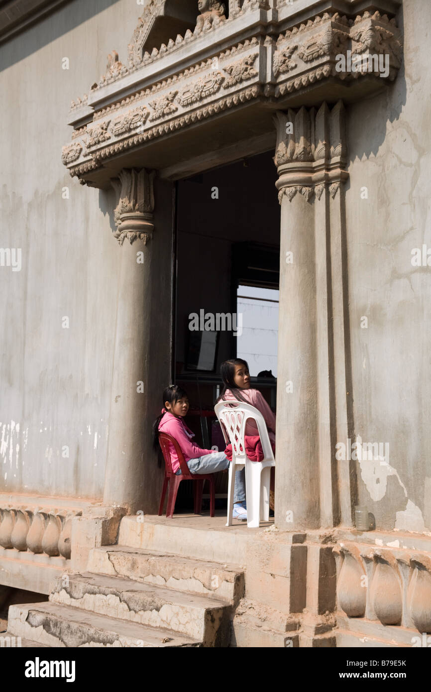 Two girl vendors, framed by the doorway, look out of the market area within Patuxai in Vientiane - Stock Image