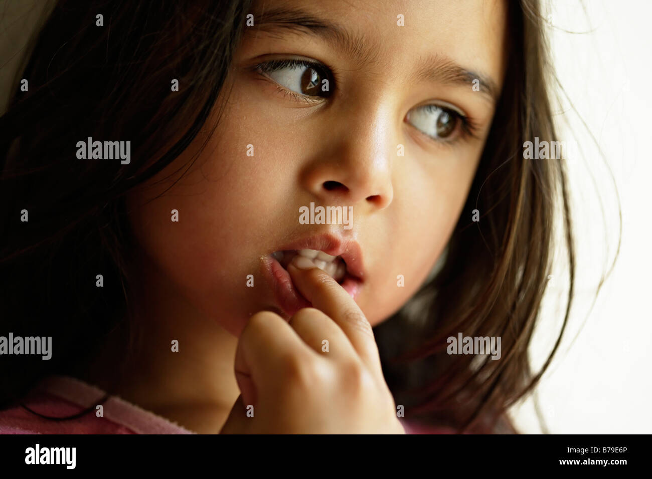 Five year old girl chews nails - Stock Image