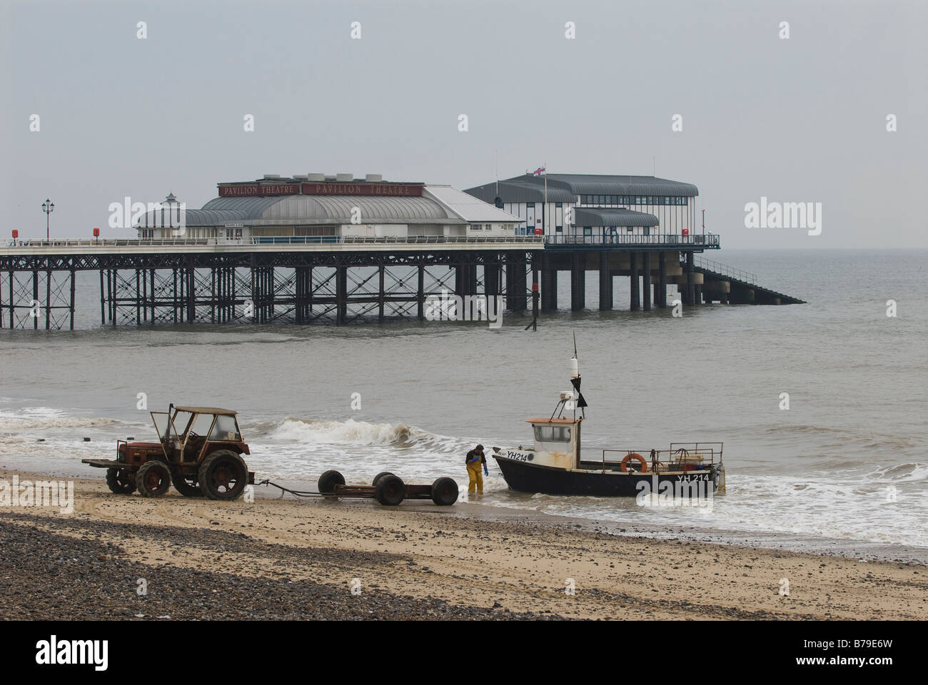A crab fisherman retrieves his boat from the sea at Cromer near to the pier. Norfolk, UK. - Stock Image