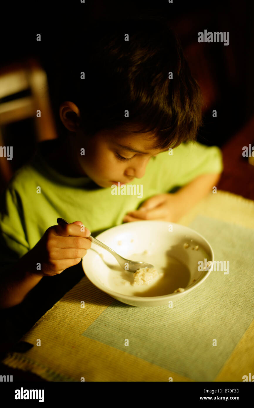 Six year old boy eating porridge at breakfast - Stock Image