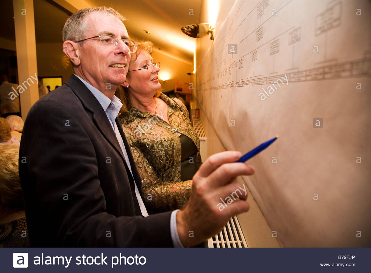 A man and a woman examine their family tree and add notations. The family memebers meet during a family re-union. - Stock Image