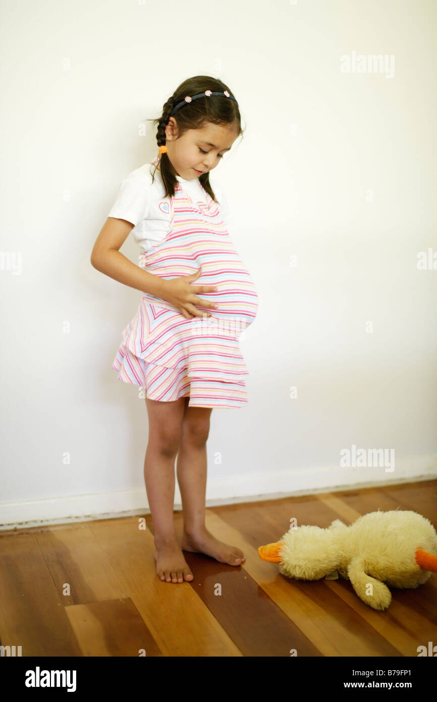 Five year old girl pretends to be fat or pregnant by stuffing a soft toy under her dress - Stock Image