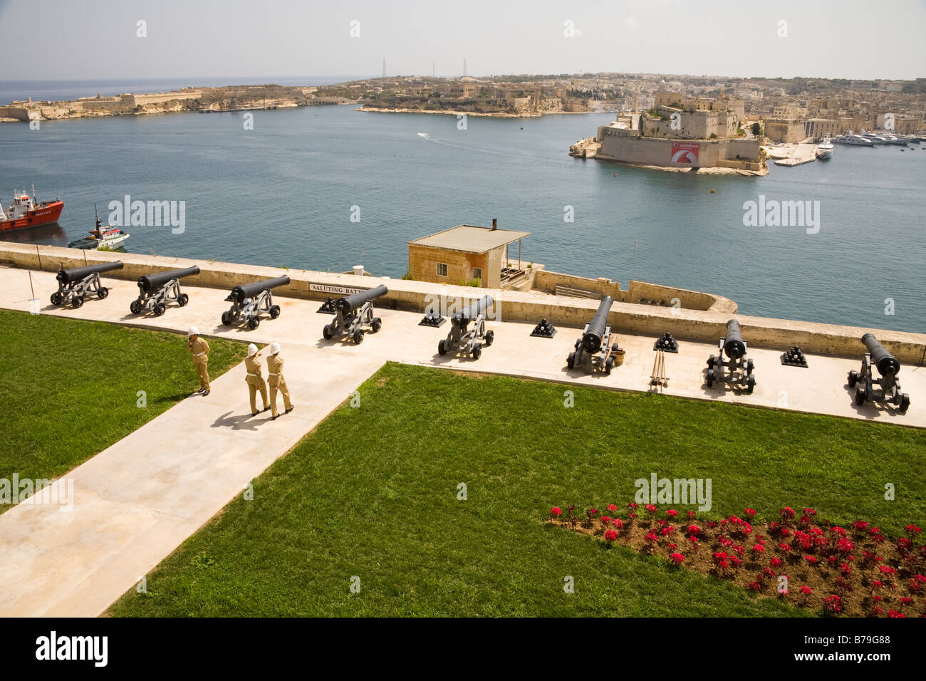 Soldiers and cannons at the Saluting Battery, and Grand Harbour, from Upper Barracca Gardens, Valletta, Malta - Stock Image