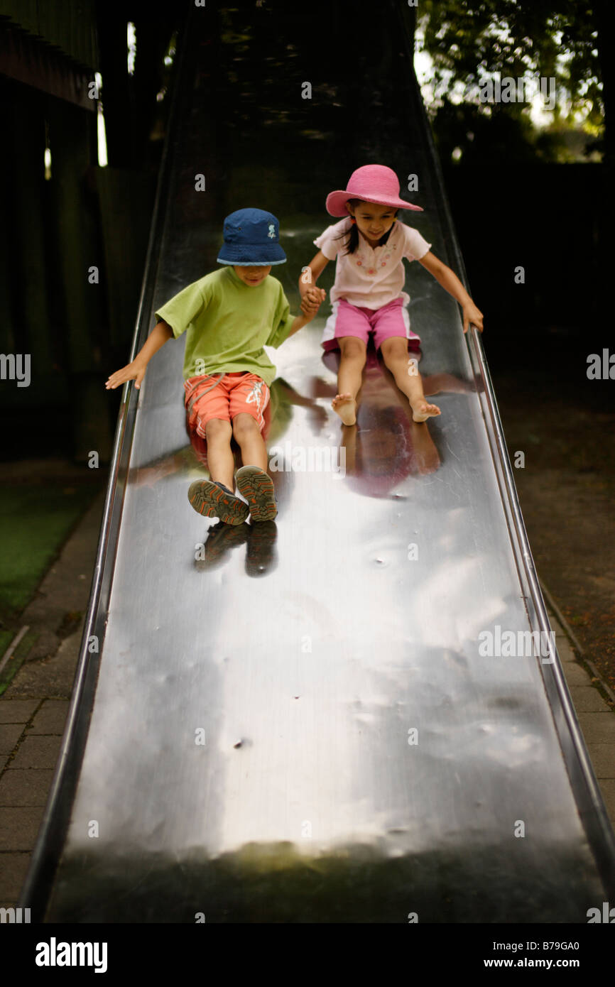 Brother aged six and sister five on wide slide - Stock Image