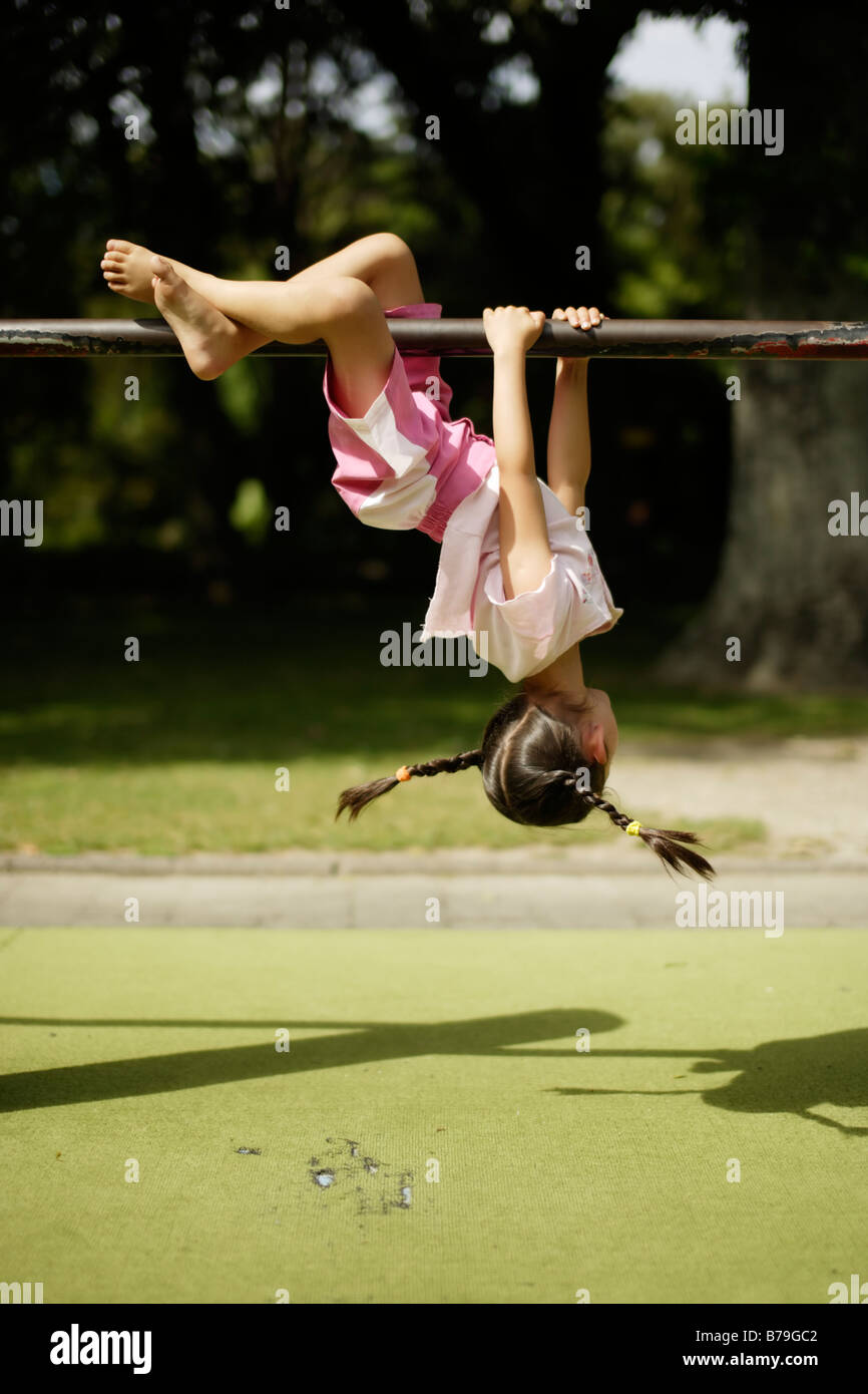 Five year old girl swings her pigtails whilst swinging upside down from a bar - Stock Image