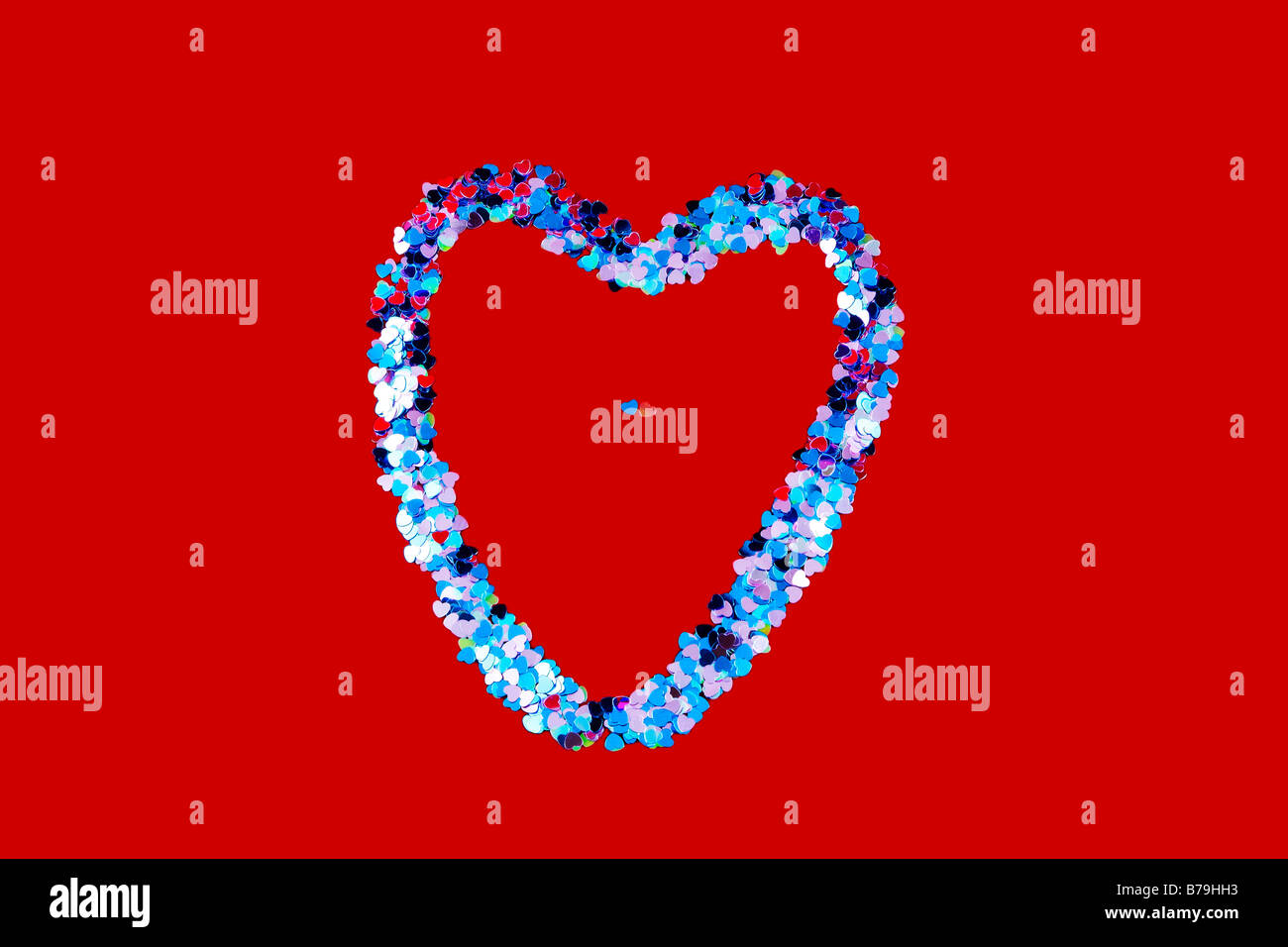Heart shape composed of heart confetti on a red background with two small hearts in the middle - Stock Image