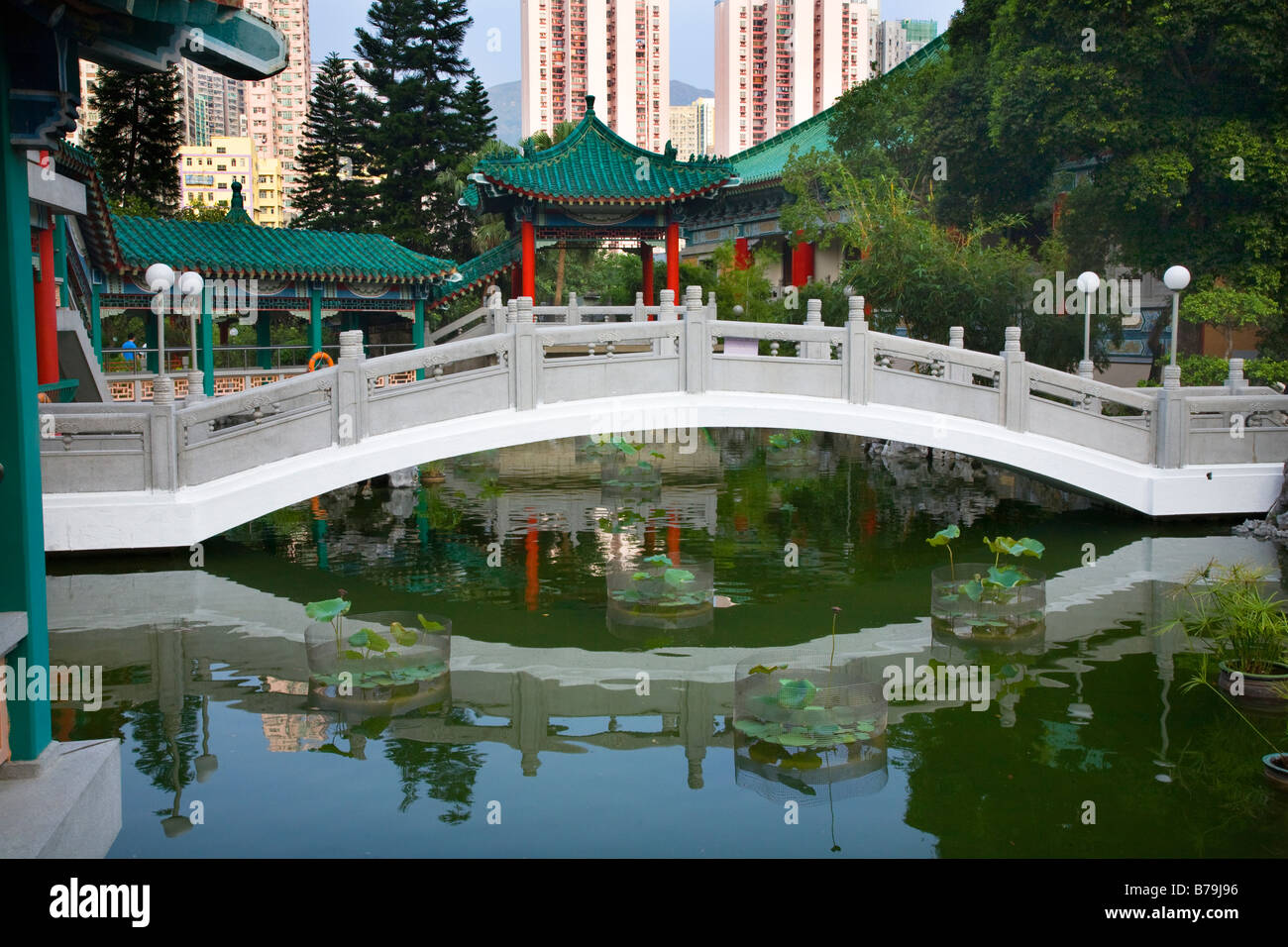 Gut Chinese Water Garden Bridge And Reflection Amid Modern High Rise Buildings  Wong Tai Sin Taoist Temple Kowloon Hong Kong