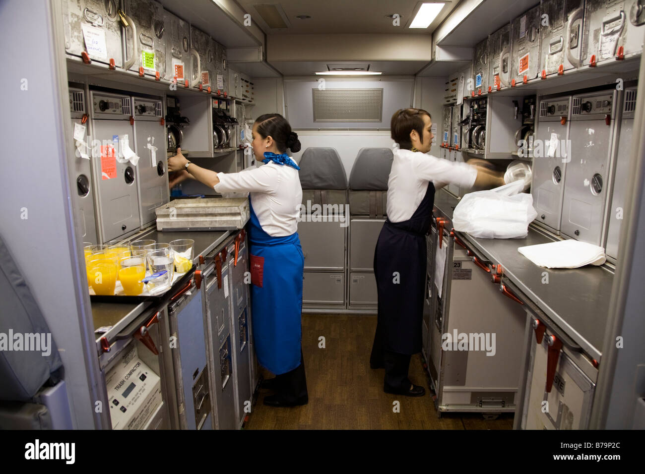 galley airplane seats two members of cabin crew working tidying in the galley 252