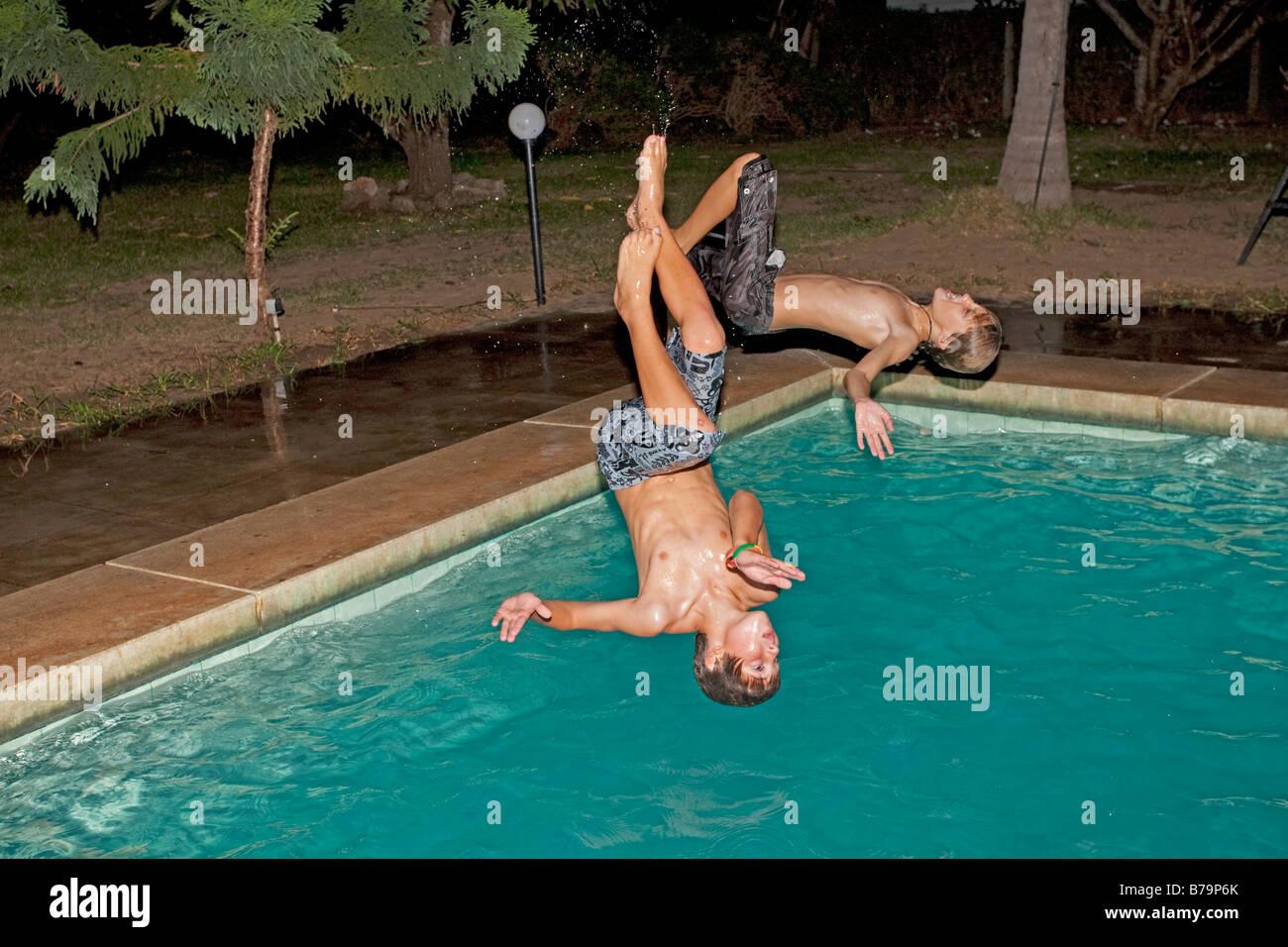 Two boys somersaulting into swimming pool Mombasa Kenya Stock Photo