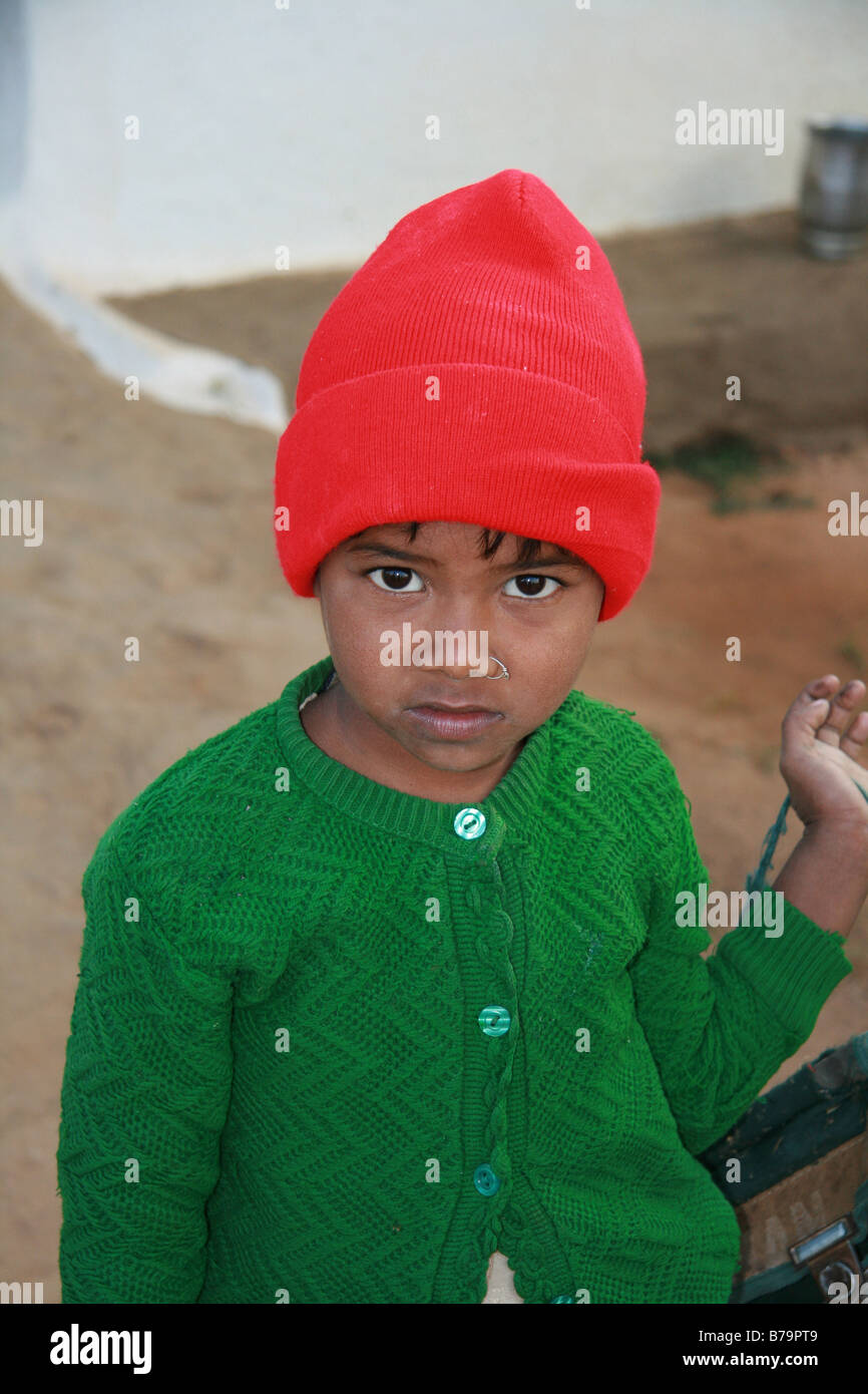 A young girl in a green cardigan and red hat outside her home in VIllage  Mocha 8a94f1f16d6c