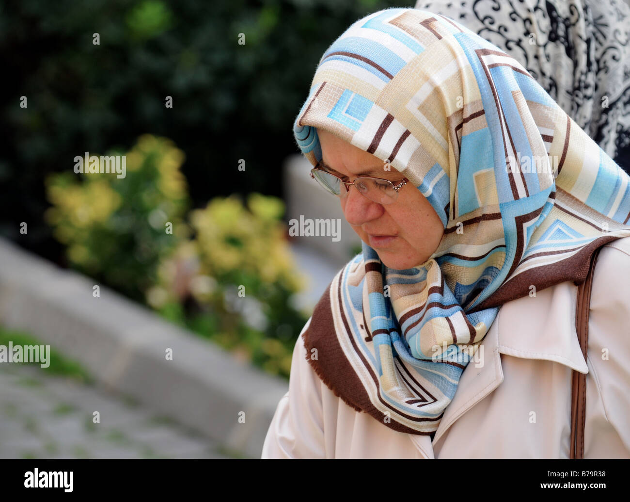 A Muslim lady visiting an important Islamic graveyard- the burial place for many previous Sultans- in Eminonu, Istanbul, Stock Photo