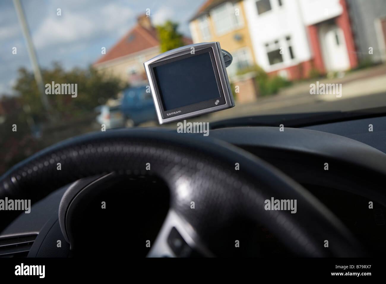 A Tom Tom satellite navigation device on a car windscreen. - Stock Image