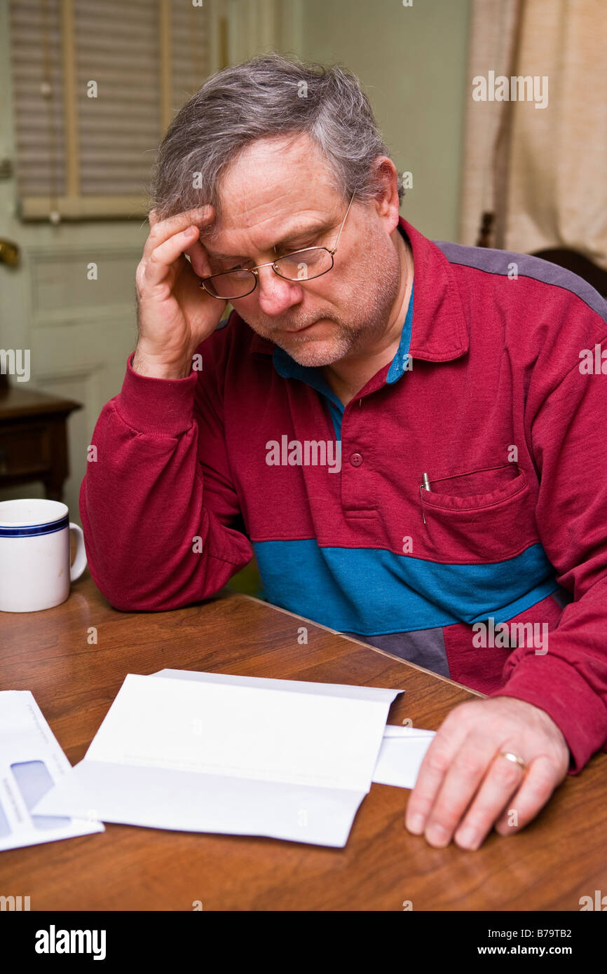 A man worries over a monthly bill - Stock Image